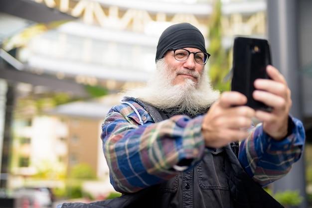 Reifer hübscher bärtiger mann, der selfie in den straßen der stadt draußen nimmt