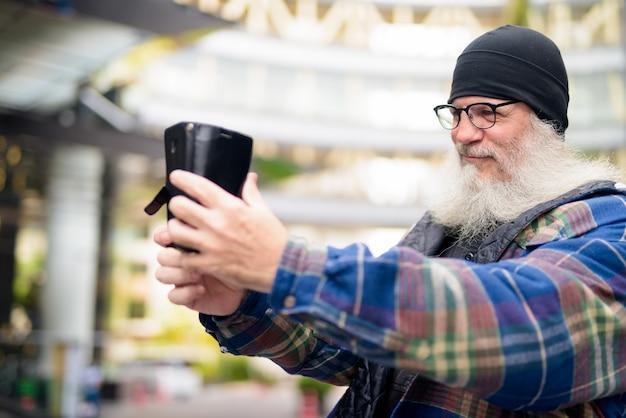 Reifer hübscher bärtiger mann, der selfie in der stadt draußen nimmt