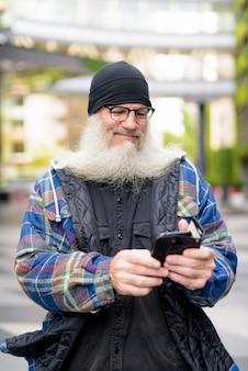 Reifer hübscher bärtiger mann, der telefon in der stadt benutzt