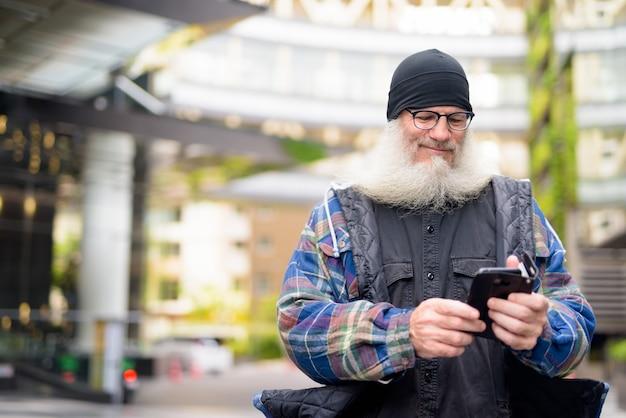Reifer hübscher bärtiger mann, der telefon in der stadt draußen verwendet