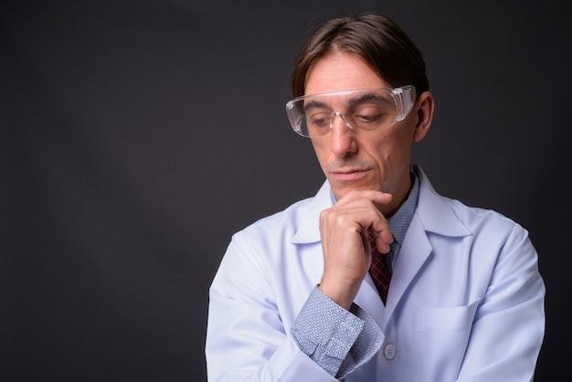 Reifer hübscher italienischer mannarzt, der schutzbrille gegen graue wand trägt