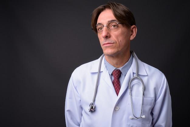 Reifer hübscher italienischer mannarzt gegen graue wand