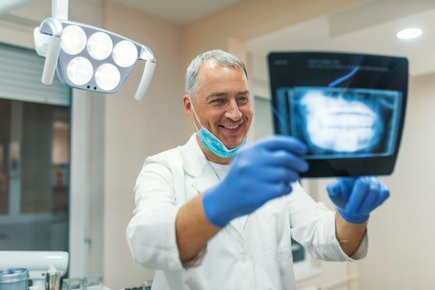 Reifer hübscher männlicher zahnarzt, der röntgenstrahlbericht in der klinik hält