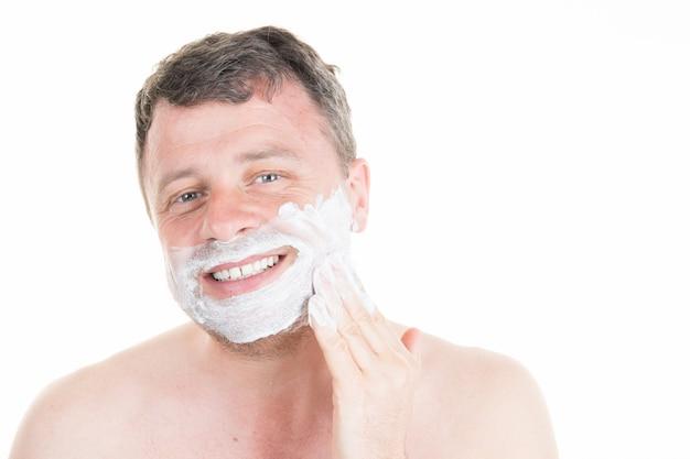 Reifer hübscher mann, der sich vor spiegel mit nacktem oberkörper rasiert