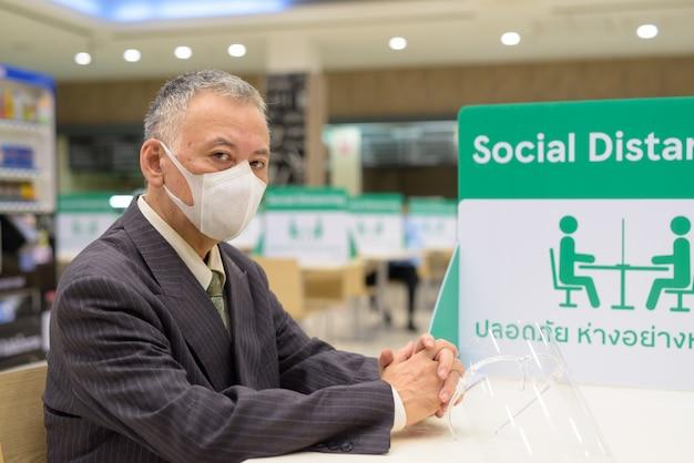 Reifer japanischer geschäftsmann, der maske trägt und mit abstand am food court sitzt