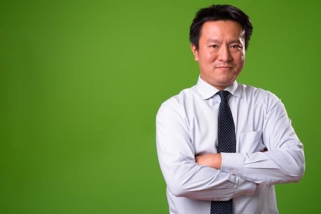 Reifer japanischer geschäftsmann gegen grünen hintergrund