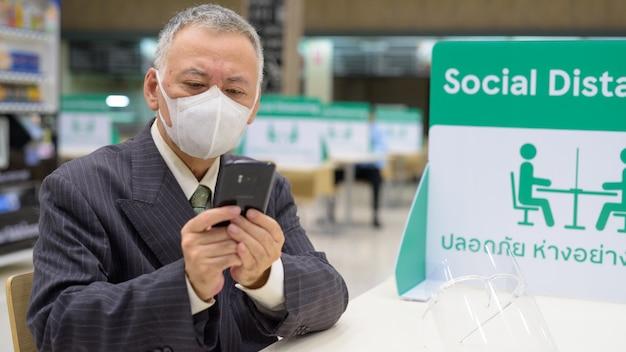 Reifer japanischer geschäftsmann mit maske, die telefon benutzt und mit abstand am food court sitzt