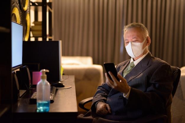 Reifer japanischer geschäftsmann mit maske, die telefon verwendet, während überstunden zu hause arbeiten