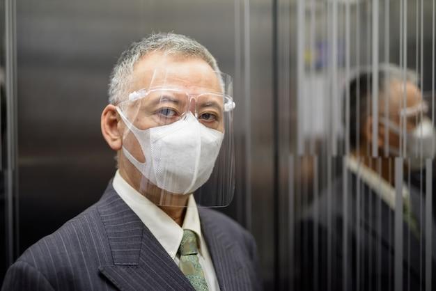 Reifer japanischer geschäftsmann mit maske und gesichtsschutz innerhalb des aufzugs