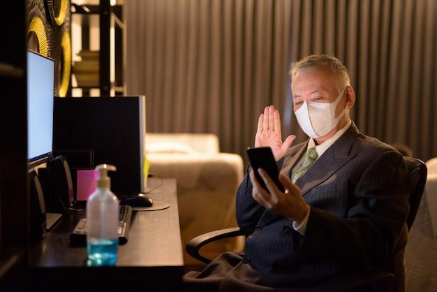 Reifer japanischer geschäftsmann mit maskenvideoanruf unter verwendung des telefons, während überstunden zu hause arbeiten