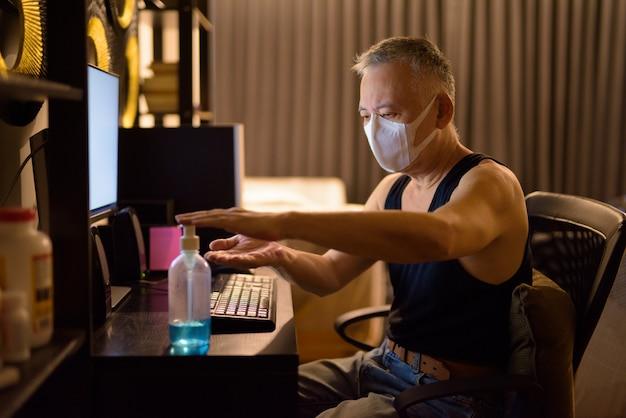 Reifer japanischer mann mit maske, die händedesinfektionsmittel verwendet, während überstunden zu hause arbeiten