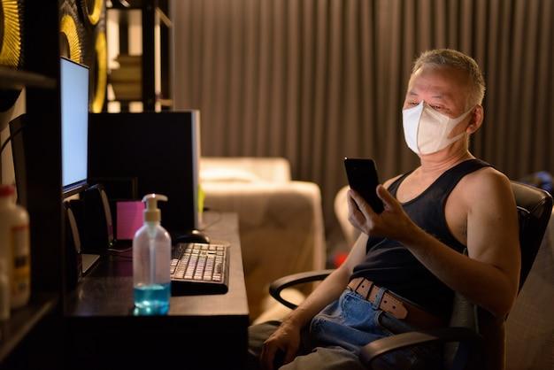 Reifer japanischer mann mit maske, die telefon verwendet, während überstunden zu hause arbeiten