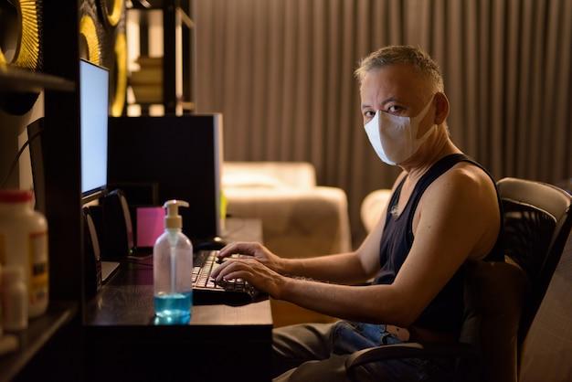 Reifer japanischer mann mit maske, die überstunden zu hause arbeitet