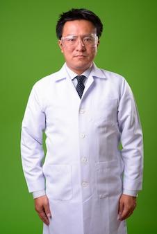 Reifer japanischer mannarzt, der schutzbrille gegen grünen hintergrund trägt