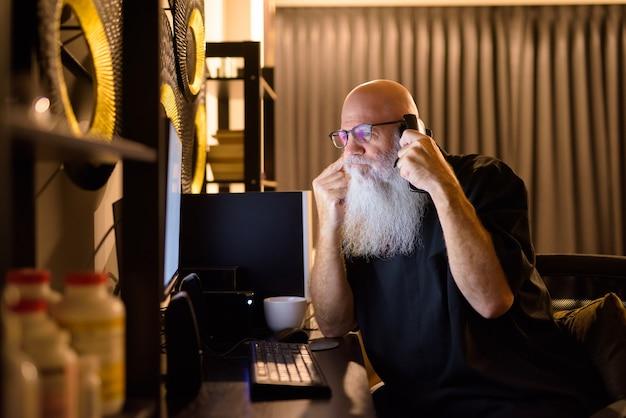Reifer kahlköpfiger bärtiger mann, der denkt und am telefon spricht, während er spät in der nacht überstunden zu hause macht