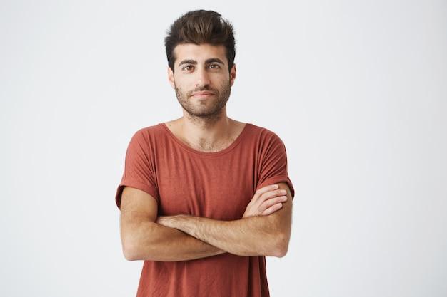 Reifer kaukasischer student, der sanft lächelt, die hände kreuzt und selbstbewusst nach einem artikel über sein start-up-projekt schießt. mann im roten t-shirt, das stolz und erfolgreich fühlt