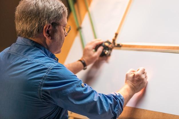 Reifer kreativer ingenieur, der mit projekt auf zeichenbrett arbeitet