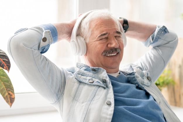 Reifer lächelnder entspannter mann, der musik in kopfhörern genießt, während er seine hände auf hinterkopf im büro hält