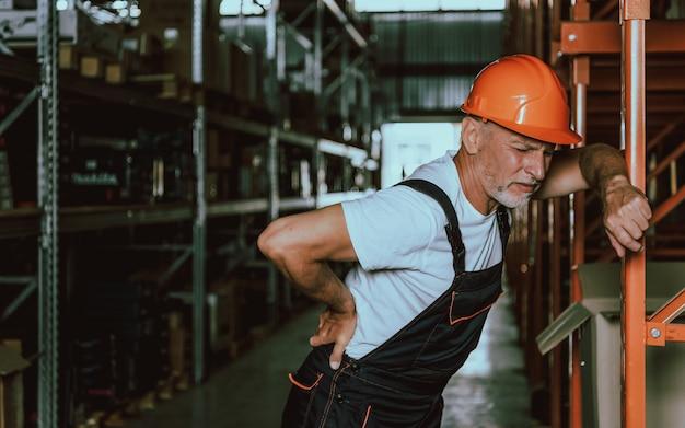 Reifer lagerarbeiter mit rückenschmerzen an arbeitsplatz