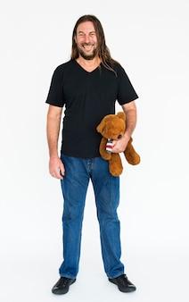 Reifer langhaariger kerl, der einen teddybären hält