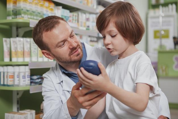 Reifer männlicher apotheker, der kleinem jungen an der drogerie hilft
