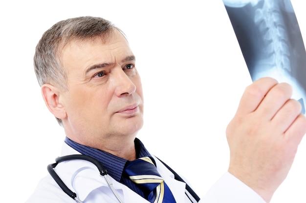 Reifer männlicher arzt, der auf dem röntgenbild schaut - lokalisiert auf weiß