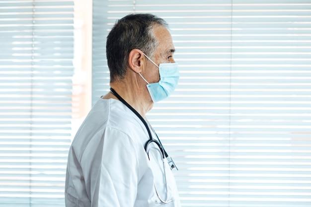 Reifer männlicher arzt - krankenschwester, die gesichtsmaske in einem krankenhausfenster trägt. covid-19 und medizinkonzept