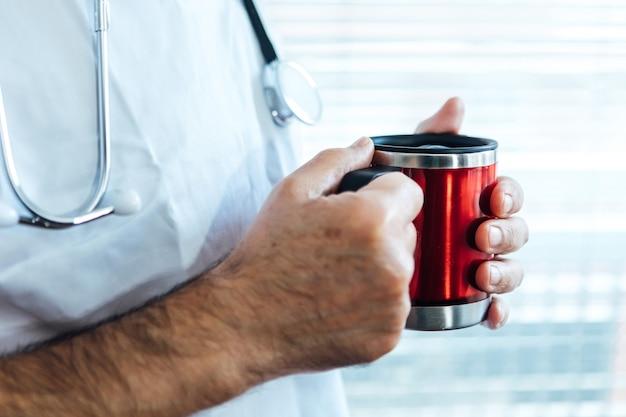 Reifer männlicher arzt - krankenschwester, die kaffee in einem krankenhausfenster trinkt. covid-19 und medizinkonzept