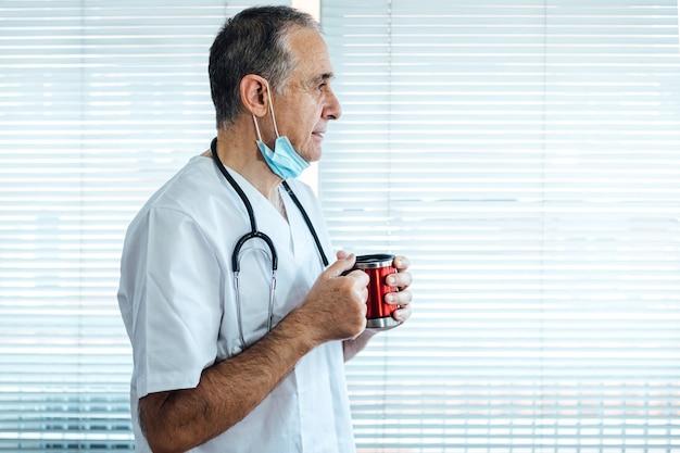 Reifer männlicher arzt - krankenschwester, die maske auf seinem kinn trägt kaffee in einem krankenhausfenster. covid-19 und medizinkonzept