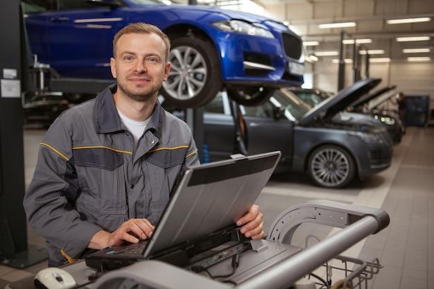 Reifer männlicher automechaniker, der an der garage arbeitet