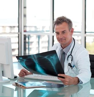 Reifer männlicher doktor, der einen röntgenstrahl überprüft