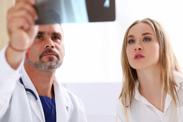 Reifer männlicher doktorgriff im arm und blick auf röntgenstrahl