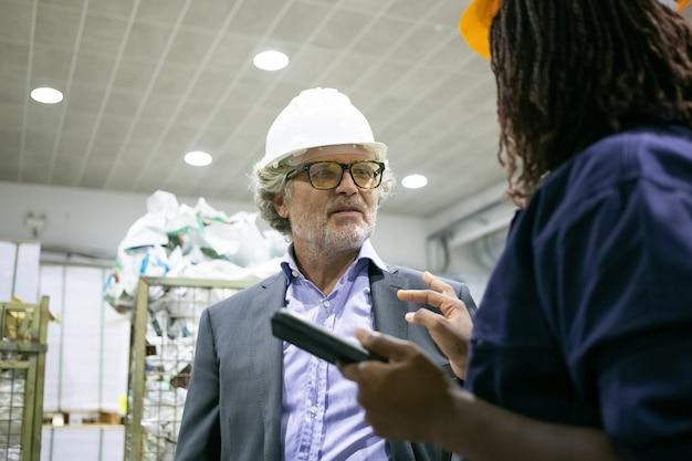 Reifer männlicher fabrikingenieur und weiblicher arbeiter, der auf werksboden an der steuerplatine der maschine spricht