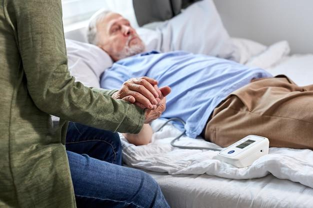 Reifer männlicher patient im krankenhaus mit besorgter frau, die mit ihm sitzt, während blutdruck mit tonometer prüft. frau hilft, unterstützt. konzentrieren sie sich auf die hände