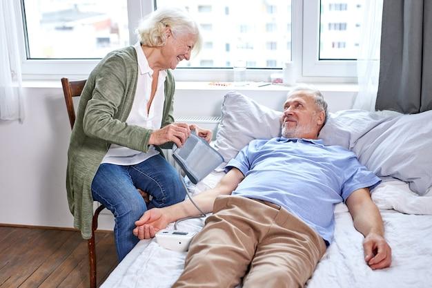 Reifer männlicher patient im krankenhaus mit besorgter frau, die mit ihm sitzt, während blutdruck mit tonometer prüft. frau hilft, unterstützt