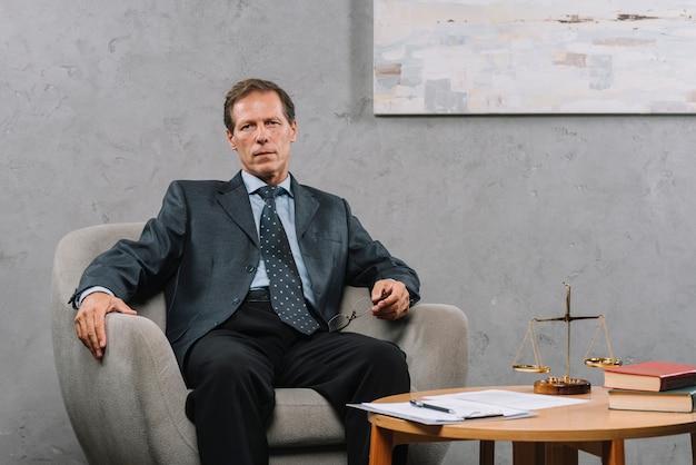 Reifer männlicher rechtsanwalt, der auf lehnsessel im gerichtssaal sitzt