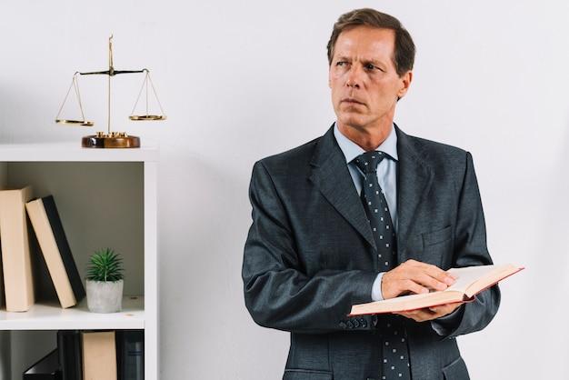 Reifer männlicher rechtsanwalt, der das gesetzesbuch steht im gerichtssaal hält