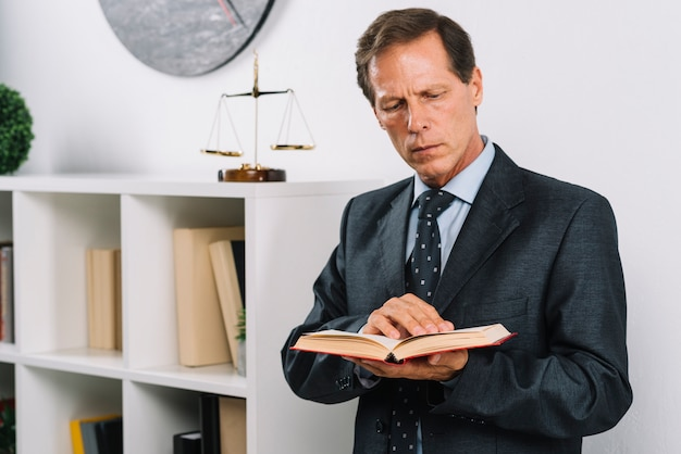 Reifer männlicher rechtsanwalt, der das rechtsbuch steht im gerichtssaal liest