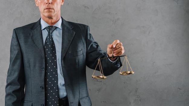 Reifer männlicher rechtsanwalt, der gerechtigkeitsskala gegen grauen strukturierten hintergrund hält