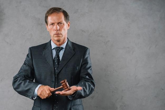 Reifer männlicher rechtsanwalt, der hammer über seiner palmenhand gegen grauen strukturierten hintergrund schlägt