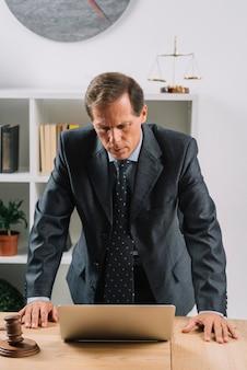 Reifer männlicher rechtsanwalt, der laptop auf schreibtisch betrachtet
