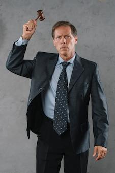 Reifer männlicher rechtsanwalt, der mit hammer gegen grauen strukturierten hintergrund schlägt