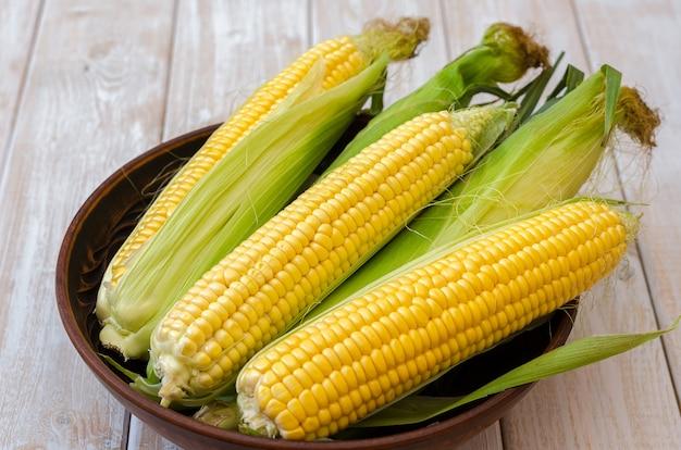Reifer mais in einer lehmschüssel auf einem hellen hölzernen hintergrund.