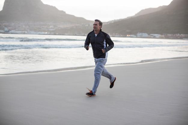 Reifer mann, der am strand joggt