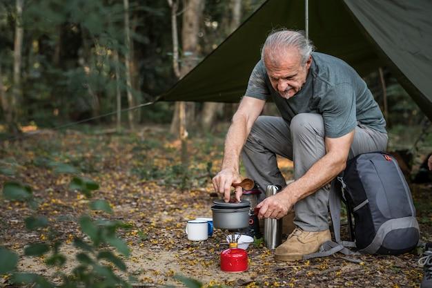 Reifer mann, der an einem campingplatz kocht