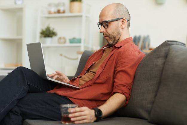 Reifer mann, der auf dem sofa sitzt, der laptop-computer benutzt und whisky trinkt, den er zu hause arbeitet