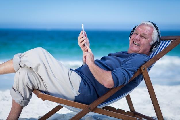 Reifer mann, der auf einem klappstuhl hört musik mit smartphone stillsteht