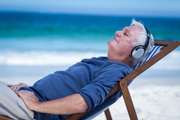 Reifer mann, der auf einem klappstuhl hört musik stillsteht