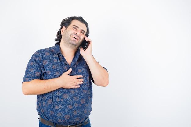 Reifer mann, der auf handy im hemd spricht und glückliche vorderansicht schaut.