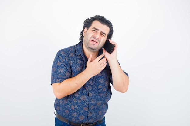 Reifer mann, der auf handy im hemd spricht und wehmütig schaut. vorderansicht.